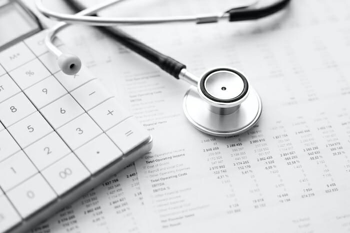 stethoscope with calculator and business paperwork